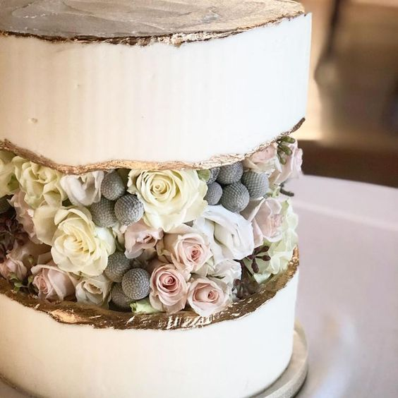 a white wedding cake with a fault line covered with fresh neutral blooms and a gold edge is a lovely and romantic idea