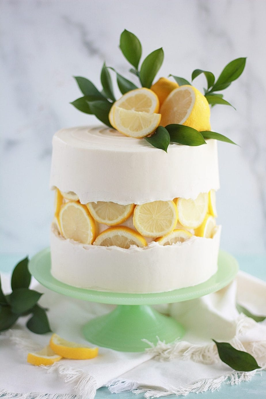 a white wedding cake with a fresh lemon fault line, topped with lemons too and some greenery for a tropical or just summer wedding