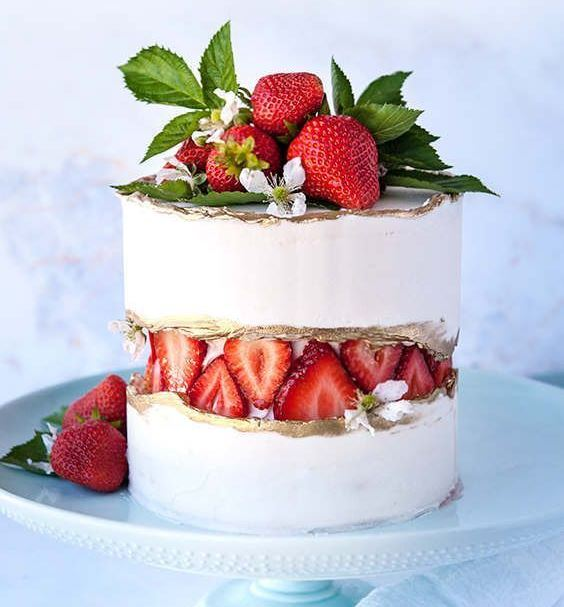 a white wedding cake with a fresh strawberry fault line, a gold edge and fresh berries and greenery on top is very yummy