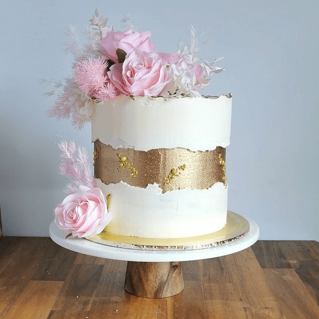 a white wedding cake with a gilded fault line with beads, pink blooms and white foliage on top looks ethereal and romantic