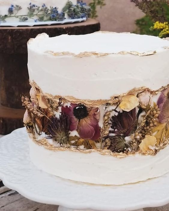 a white wedding cake with a gold edge and a fault line covered with dried blooms and foliage is very refined