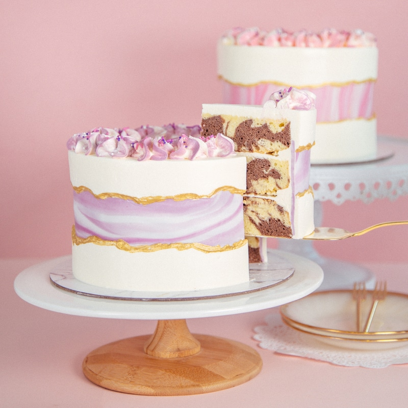 a white wedding cake with a lilac marble failt line and marble inside plus some meringues on top is amazing