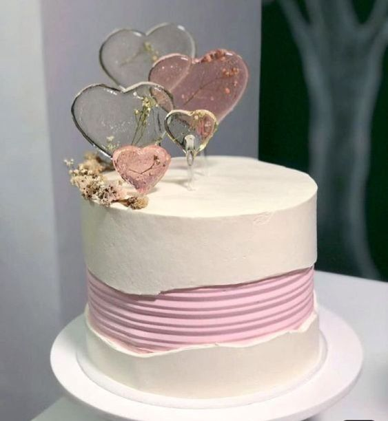 a white wedding cake with a pink striped fault line, sheer sugar hearts with dried blooms on top