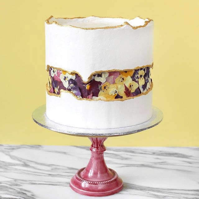 a white wedding cake with a pressed flower design and a gold edge   these violas are completely edible