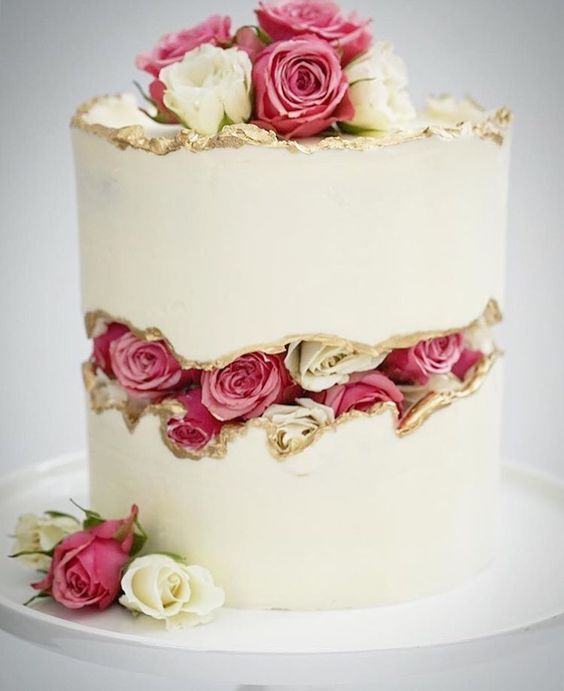 a white wedding cake with a rose fault line and some roses on top is a fresh take on a classic wedding cake