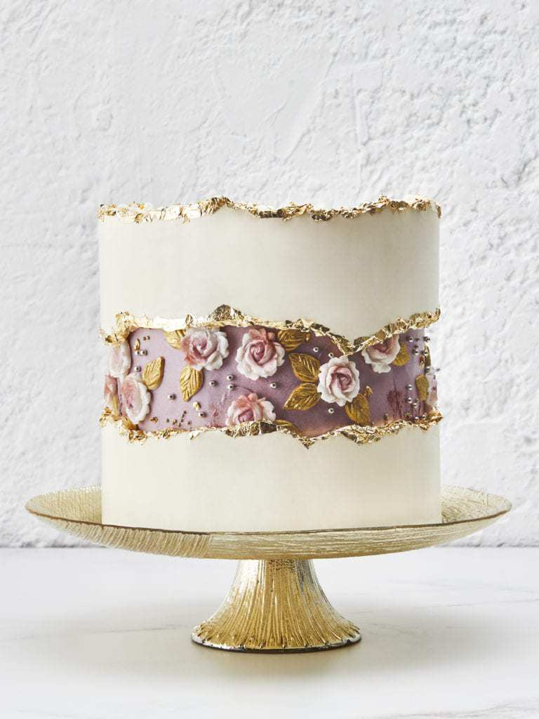 a white wedding cake with a whimsical purple 3D flower fault line accented with gold leaf is gorgeous