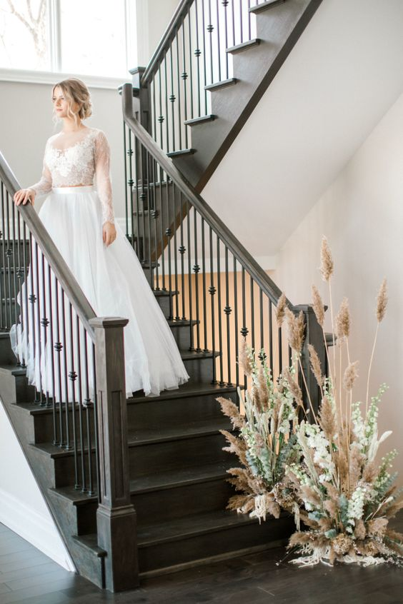 an at home wedding with a decorated staircase, with greenery and pampas grass is a lovely idea