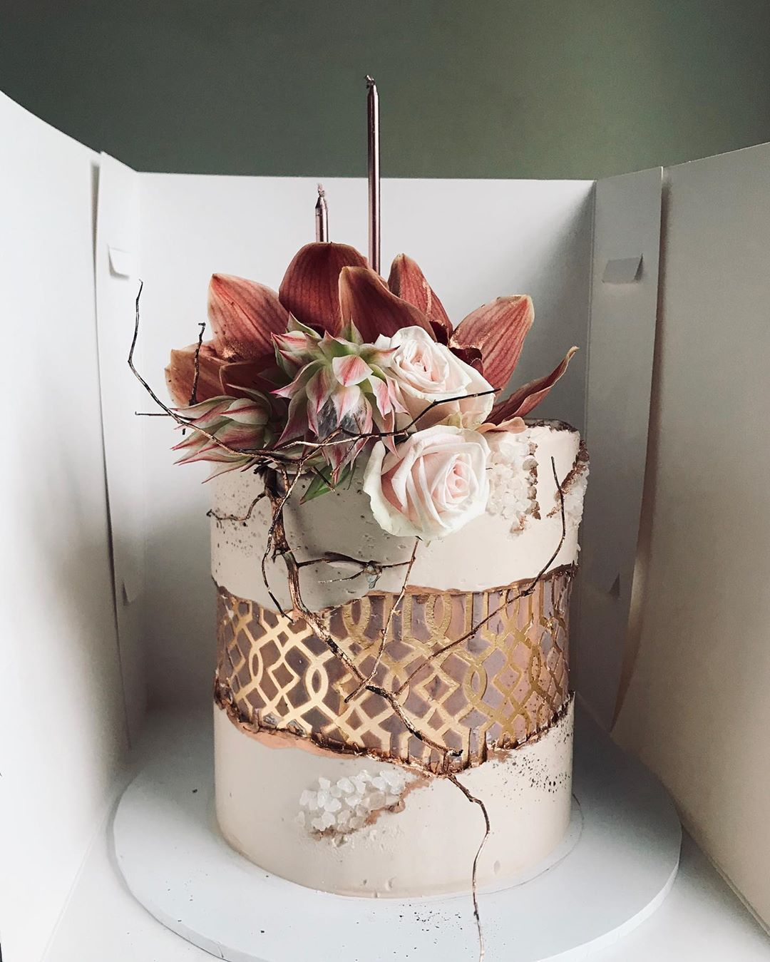 an exquisite blush wedding cake with a delicate patterned fault line, with cracks, mauve and pink blooms and a copper twig