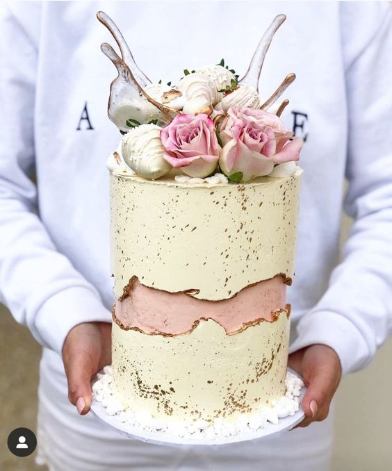 an ivory wedding cake with a pink fault line and gold splatters, pink roses, strawberries and splashes of caramel on top