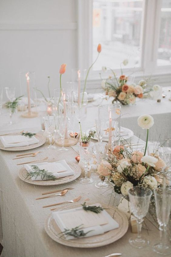 a beautiful Scandinavian spring tablescape with neutral linens, greenery, pastel and white blooms and glasses and candles