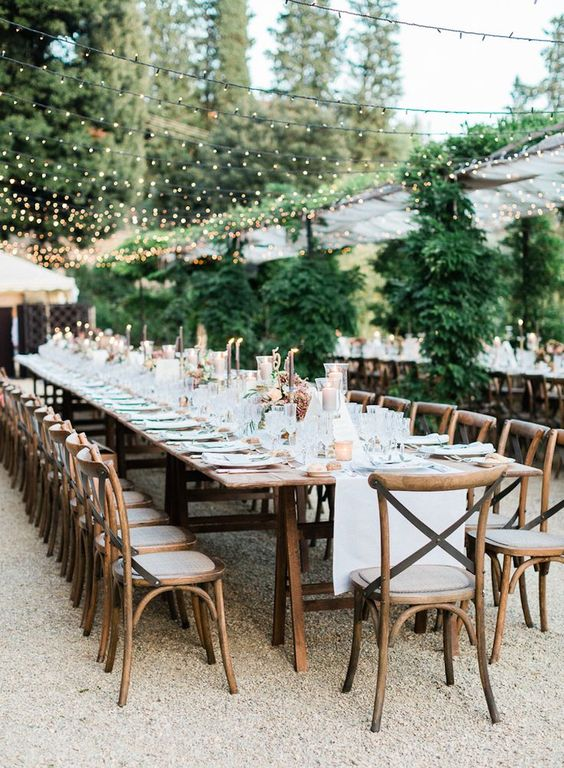 a beautiful al fresco wedding reception in neutrals, with candles and a light canopy plus neutral linens is chic