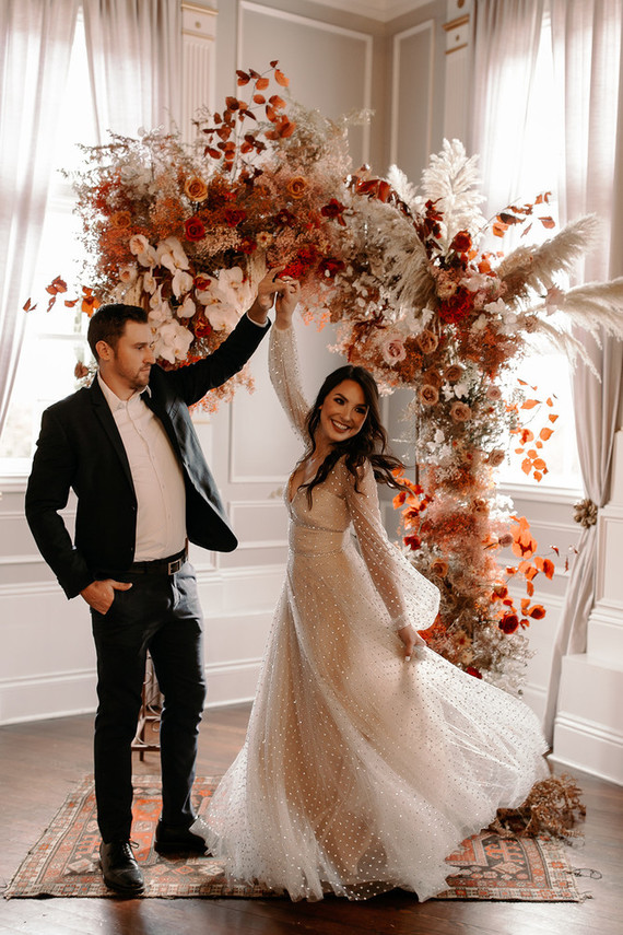 a beautiful boho wedding arch with red, burgundy, rust, orange blooms, bold fall leaves and pampas grass