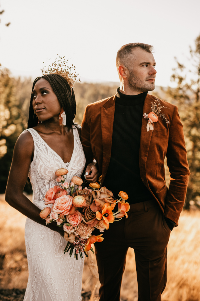a black turtleneck, brown pants, an orange velvet blazer and a bold floral and drid foliage boutonniere for a fall boho wedding