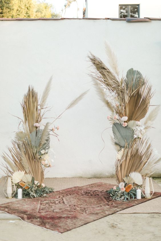 a boho wedding altar with green and tan fronds, pampas grass and white blooms plus candles on the floor