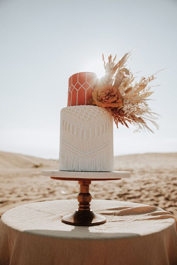 a boho wedding cake with a rust patterned and a white macrame tier, with dried foliage, blooms and herbs is chic