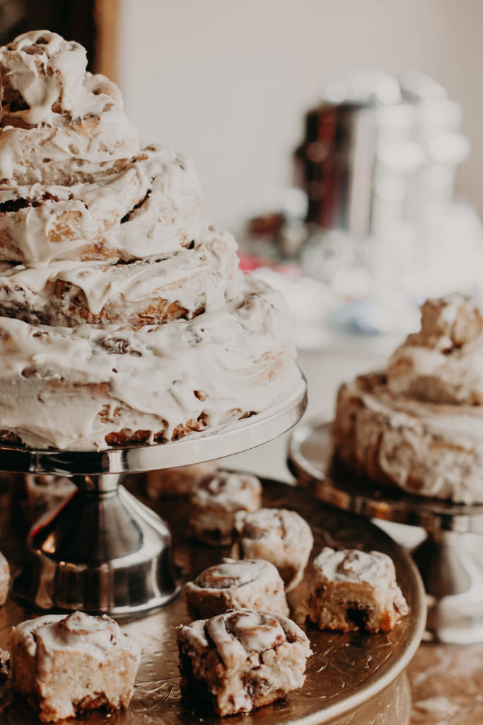 a cinnamon bun wedding cake fully covered with white icing is a delicious dessert for a relaxed wedding