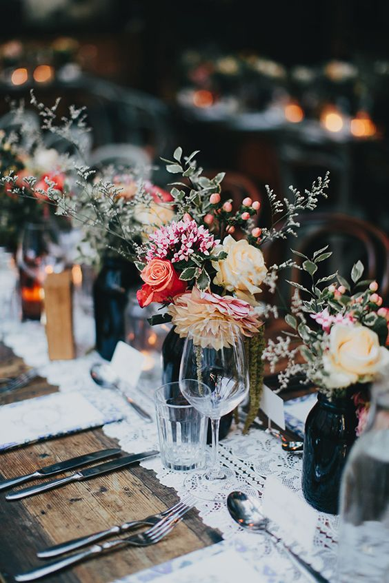 a cluster wedding centerpiece of dark bottles with bright and pastel blooms, with greenery and berries plus candles