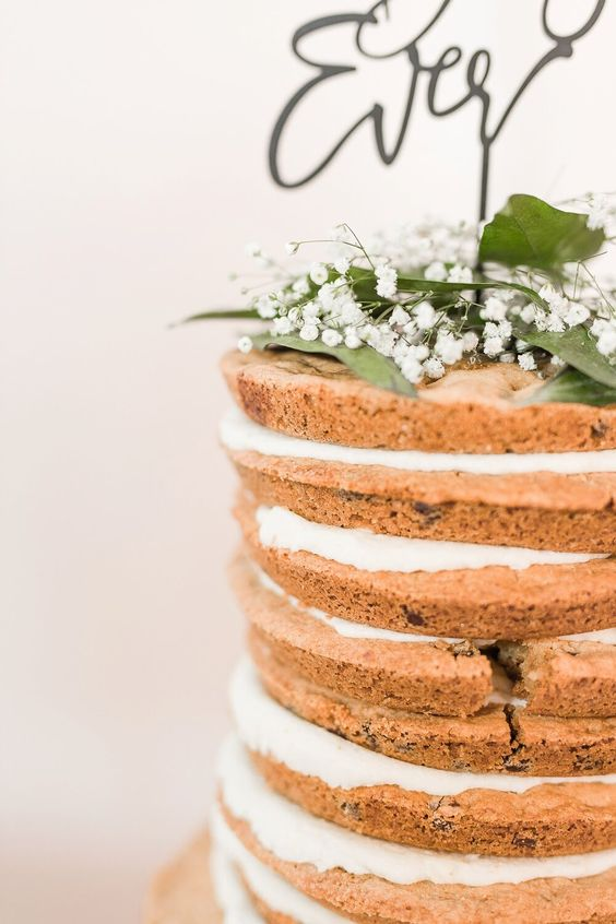 a cookie wedding cake with white filling, foliage and baby's breath plus a calligraphy topper for spring