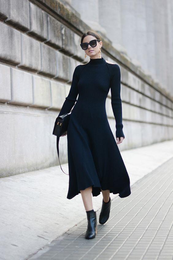 a gorgeous black fitting midi dress with cutout shoulders and long sleeves, black boots, statement earrings and a black bag