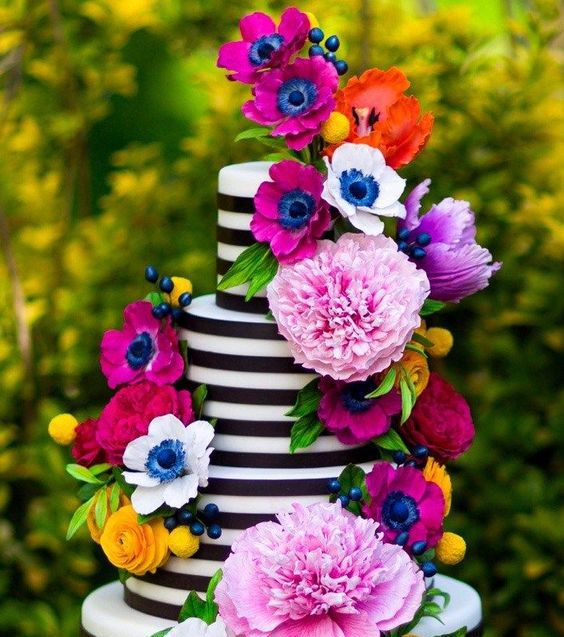 a striped black and white wedding cake decorated with bold blooms, berries and greenery is a stylish idea for a bold summer wedding