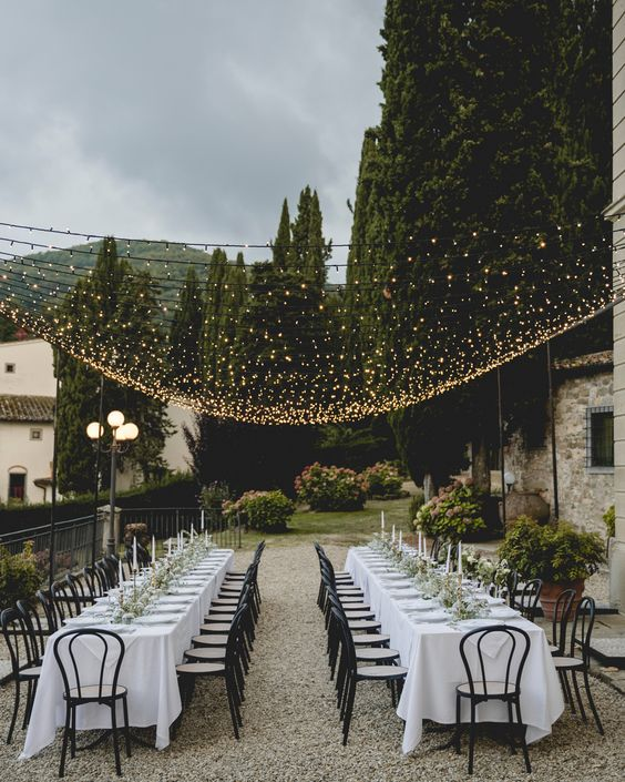 a beautiful and chic al fresco wedding reception with greenery runners and candles, with refined chairs and a warm light canopy