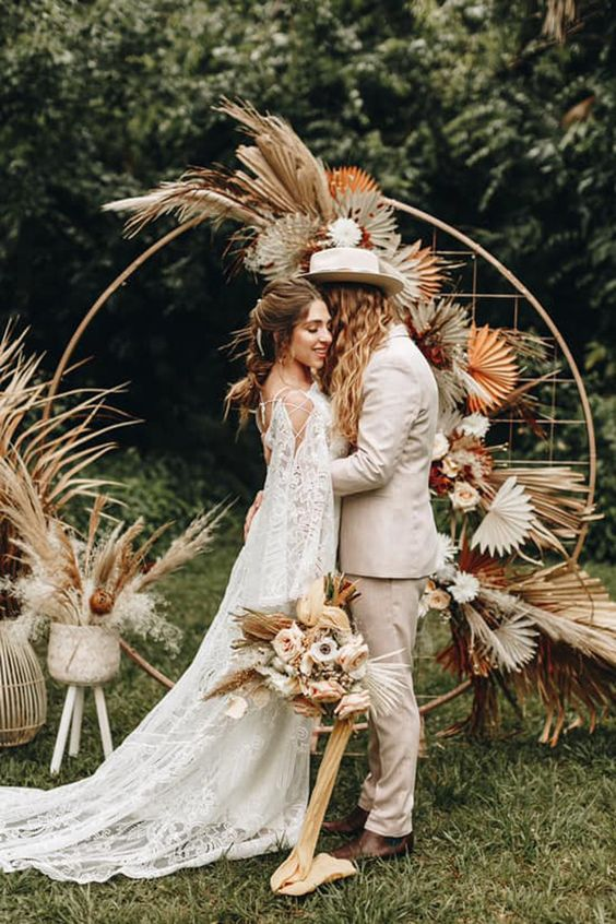 a boho wedding arch styled with fronds, usual and colored ones, pastel blooms and pampas grass for a boho wedding