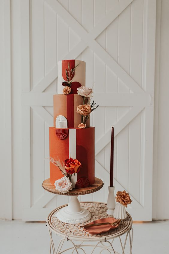 a bold orange, rust, blush wedding cake with bold blooms, feathers and grasses and bright sugar detailing for a 70s wedding