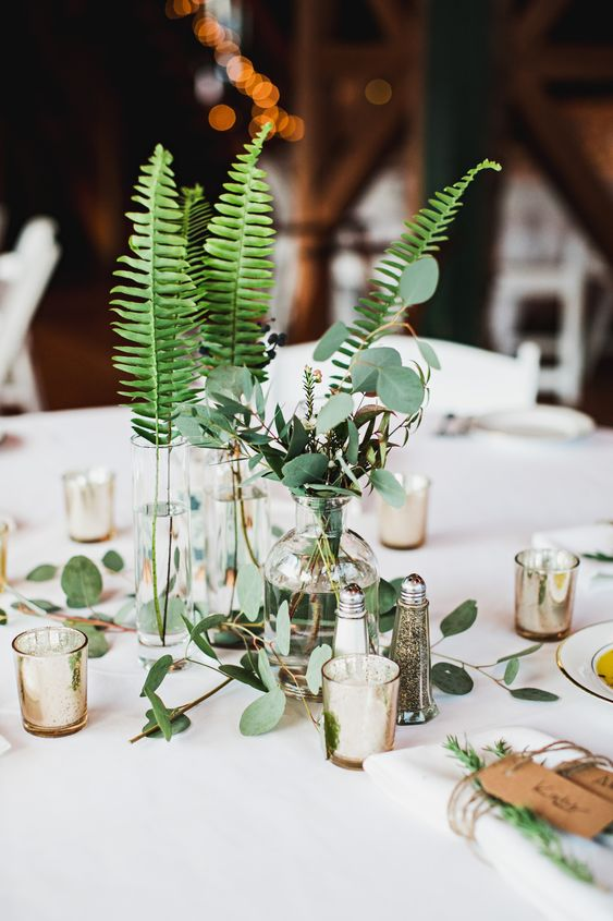 a chic cluster wedding centerpiece of vases and bottles with fern and eucalyptus plus candles around for a modern or woodland wedding