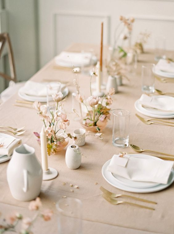 a chic modern Scandinavian table setting with various candles, pastel floral arrangements, white porcelain and gold cutlery