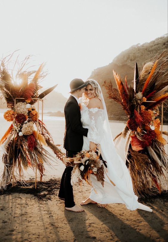 a gorgeous boho wedding altar with rust, burgundy and black pampas grass and fall-colored hydrangeas is wow