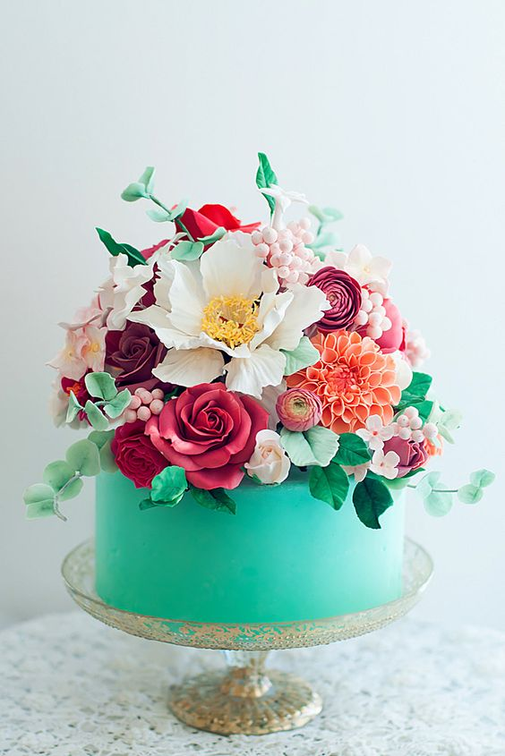 a mint blue wedding cake topped with fresh and sugar blooms in various colors and sugar leaves and foliage