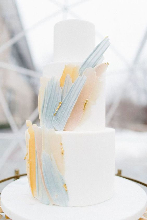 a white wedding cake accented with blue, blush and yellow brushstrokes and some gold leaf is wow