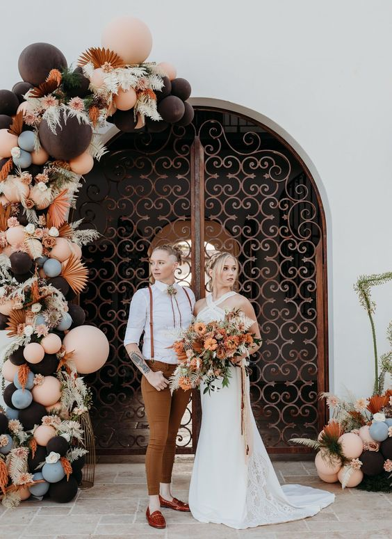 a boho wedding arch with pink, blue and black balloons, colorful fronds and pink and white blooms for a modern boho wedding