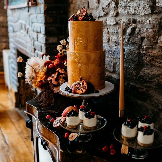 a decadent wedding cake in rust shades, with a texture and gold leaf plus fresh fruit and berries around and on top is perfect for a fall wedding