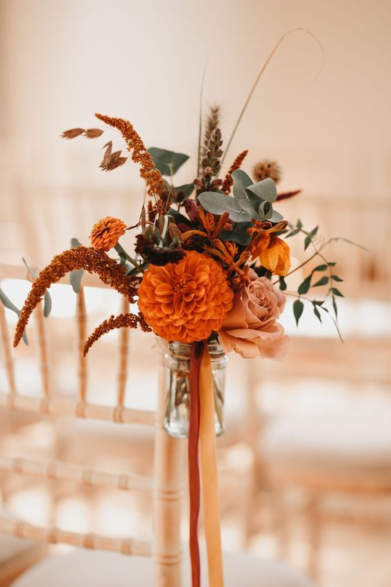 a floral arrangement of orange, rust and dusty pink blooms, greenery and twigs will be nice for aisle decor