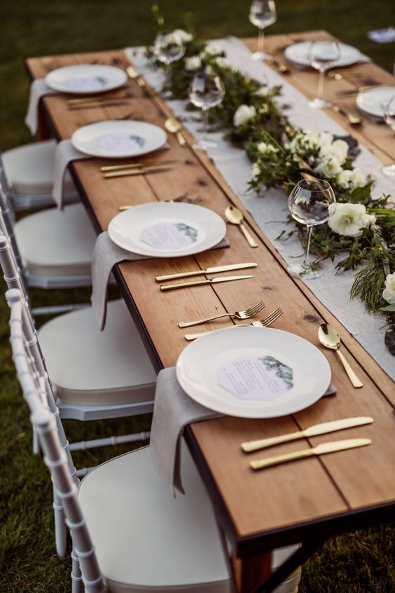 a fresh and natural wedding tablescape with neutral linens, a greenery and white blooms and gold cutlery is chic