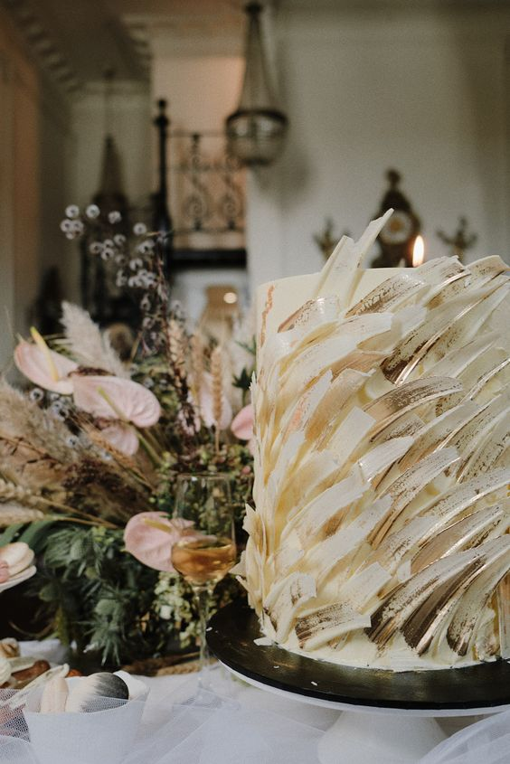 a lovely white wedding cake with white gilded brushstrokes that imitate feathers for a ballet-inspired wedding
