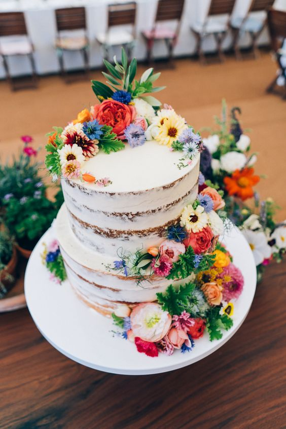 a naked wedding cake with greenery and bright fresh blooms is a lovely idea for a rustic summer wedding
