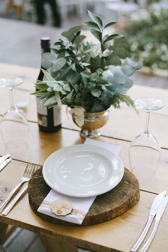 a beautiful wedding centerpiece of a silver bowl and some greenery of various kinds is ideal for a modern rustic wedding