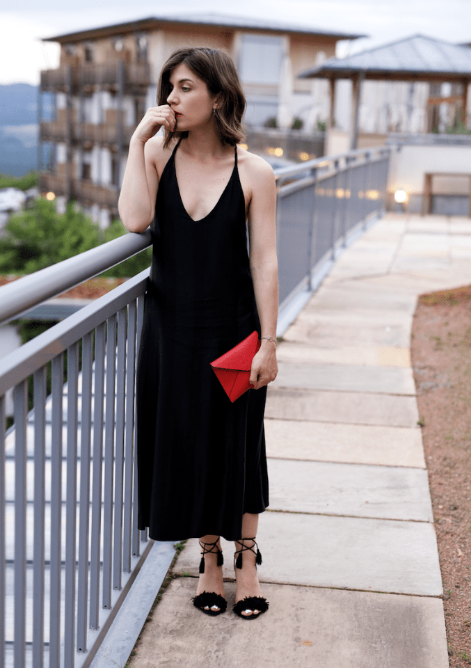 a black velvet slip midi dress with a deep neckline, black tassel shoes and a red clutch