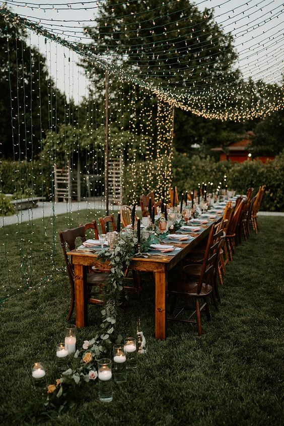 a boho chic wedding reception with a greenery and pastel runner, floating candles and a warm light canopy for an ambience