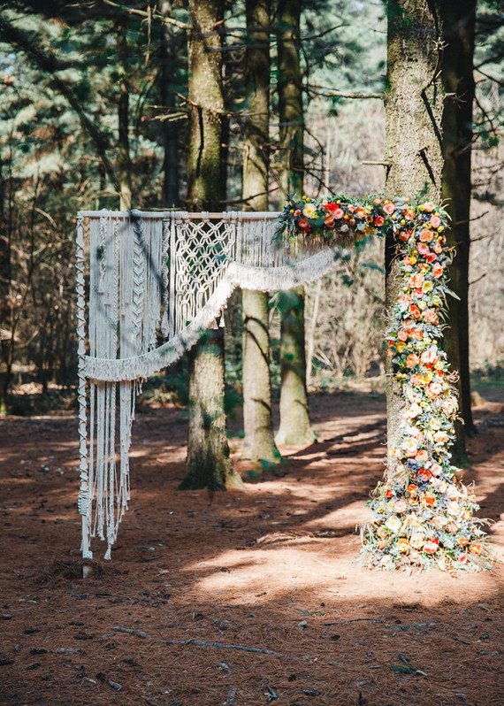 a boho wedding arch with bright blooms, greenery, macrame is a cool idea for a boho 70s wedding