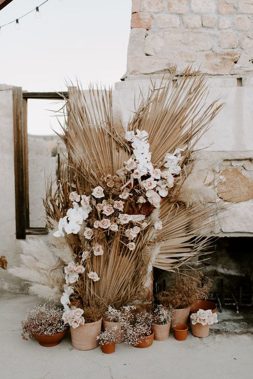 a boho wedding backdrop of an old fireplace, dried fronds, white and blush blooms and some potted plants is chic