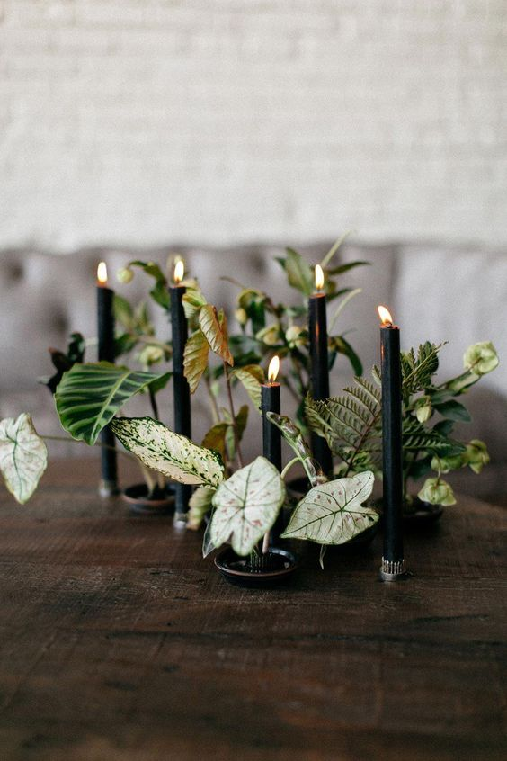 a creative botanical wedding centerpiece with leaves and black candles is a cool idea for Halloween