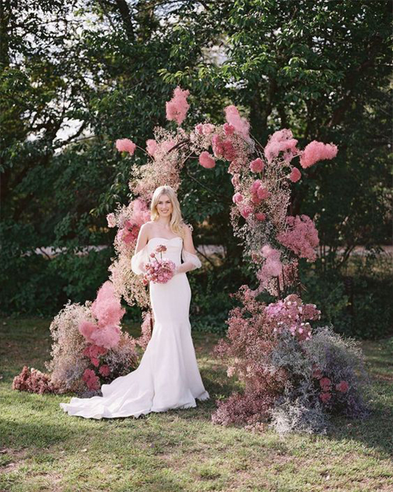 a creative wedding arch of bright pink blooms, pink and lilac baby's breath for a modern colorful wedding