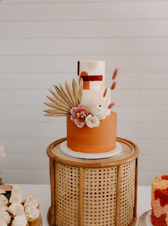 a fabulous 70s wedding cake with a terracotta tier and white ones, with color block decor, with fresh blooms and fronds and grasses