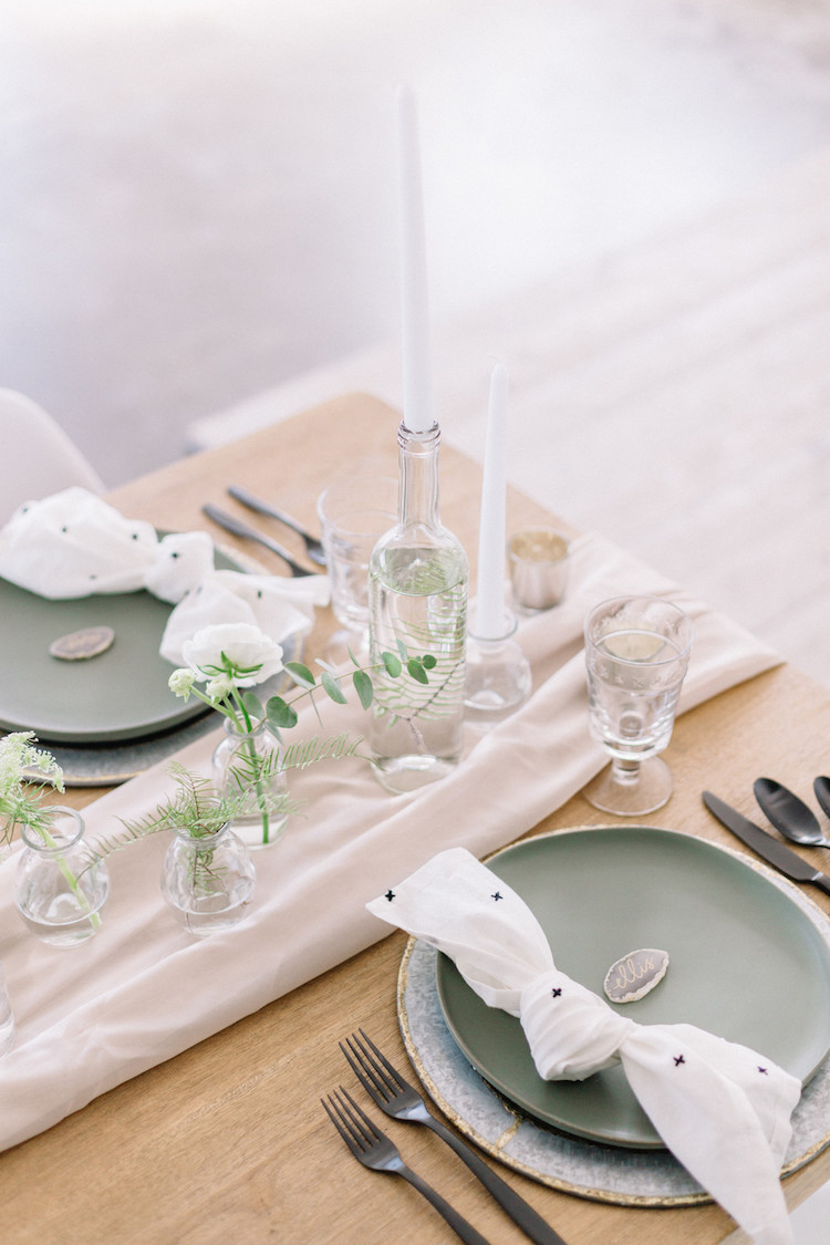 a fresh spring Scandinavian tablescape with a neutral runner and printed napkins, a cluster greenery centerpiece and candles, green plates