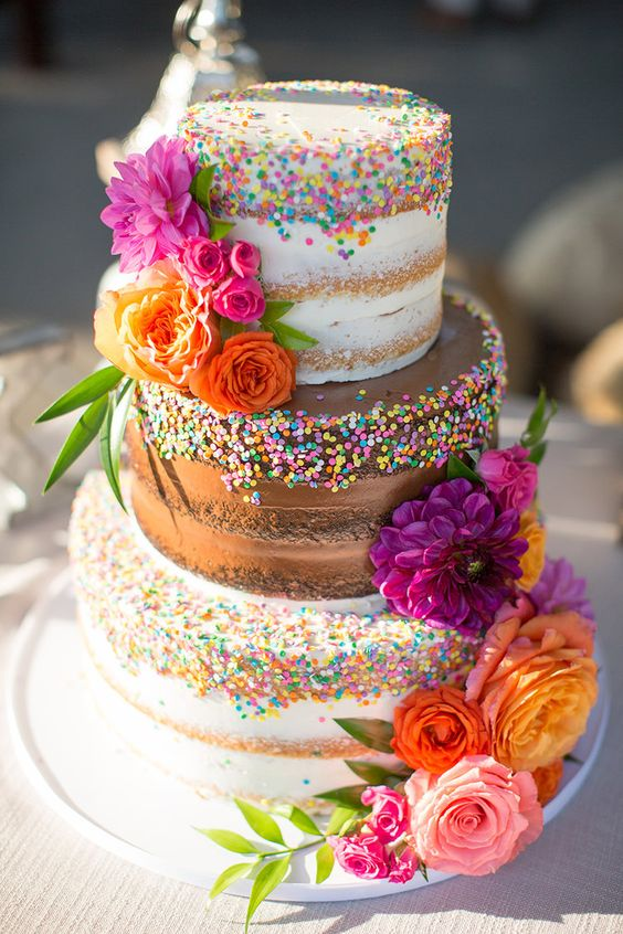 a naked wedding cake with mismatching tiers, colorful sprinkles, bold blooms and greenery is a lovely and fun idea