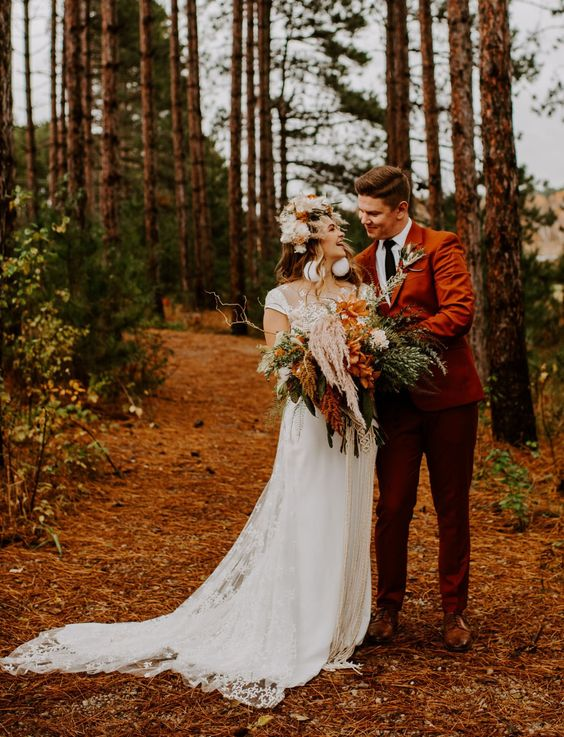 a rust suit, a white shirt, a black tie and brown shoes for a beautiful boho fall wedding and a touch of color