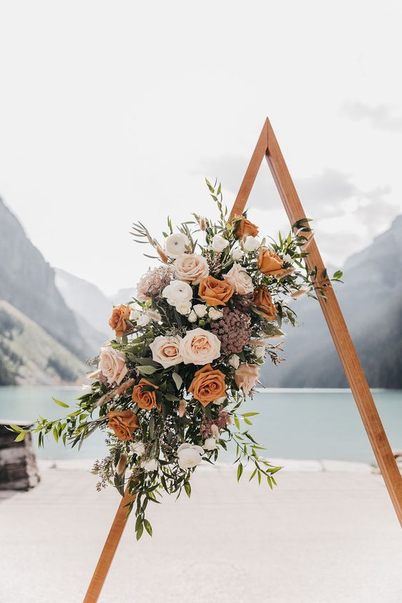 a triangle wedding arch with blush, mauve, rust blooms and greenery is a very pretty and creative idea for a fall boho wedding